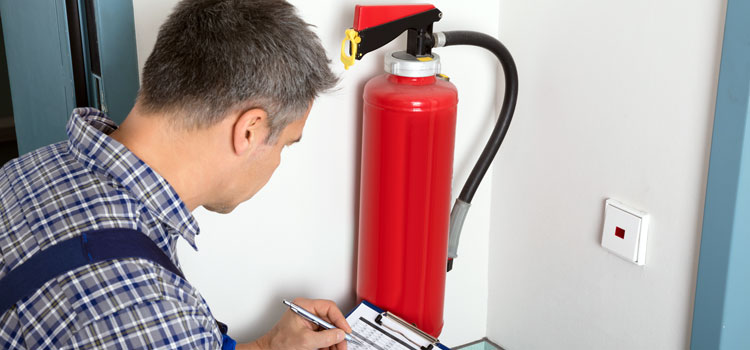 Photo of a worker carrying out a routine inspection of fire extinguishers in an office