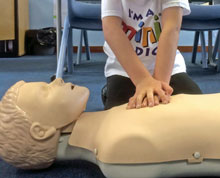 Image of a Mini Medics student practicing CPR on a dummy